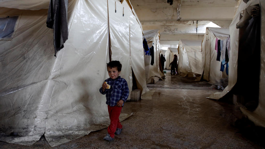 An internally displaced Syrian boy walks along tents in an IDP camp located in Idlib, Syria February 27, 2020.  REUTERS/Umit Bektas