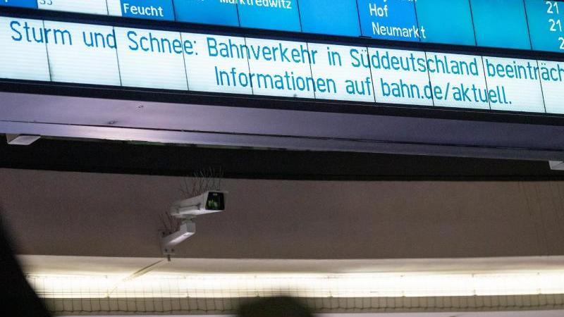 """""""Sturm und Schnee: Bahnverkehr in Süddeutschland beeinträchtigt"""" steht auf einer Anzeigetafel. Foto: Daniel Karmann/dpa"""