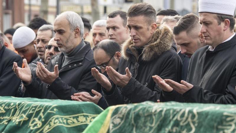 Mit einem muslimischen Totengebet an den Särgen der Opfer nehmen Menschen auf dem Marktplatz von Hanau Abschied. Foto: Boris Roessler/dpa