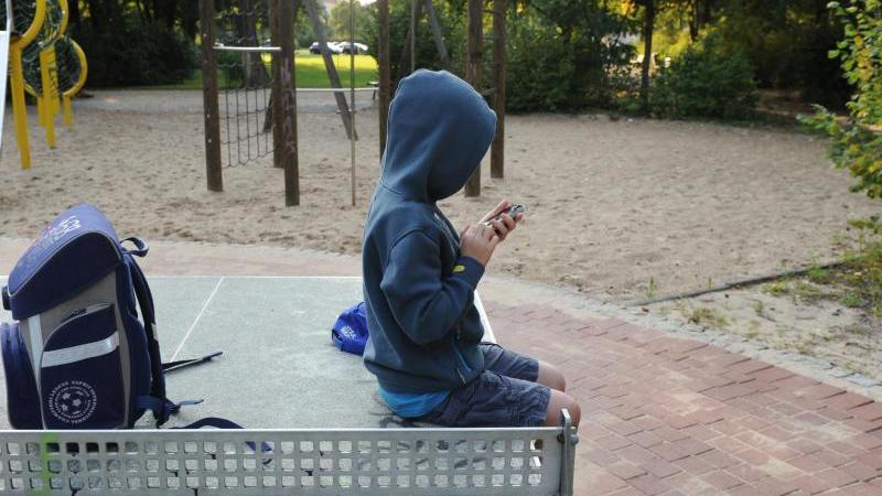 Ein Junge sitzt mit seinem Schulranzen auf einer Tischtennisplatte und spielt auf einem Smartphone. Foto: Jens Kalaene/dpa-Zentralbild/dpa/Archivbild