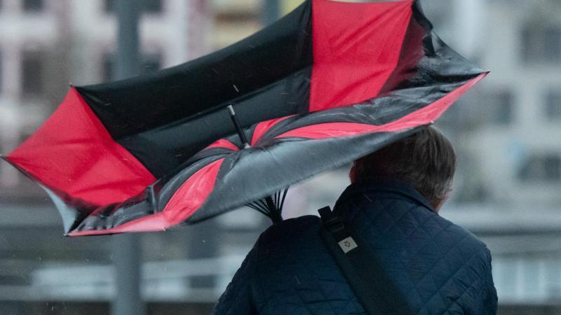 Der Regenschirm eines Spaziergängers ist wegen einer Windböe umgeklappt. Foto: Bernd Thissen/dpa/Archivbild
