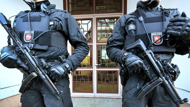 Bewaffnete Polizeibeamte sichern einen Eingang zum Oberlandesgericht (OLG). Foto: Holger Hollemann/dpa