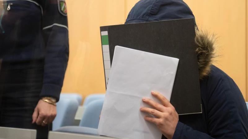 Die Angeklagte, eine mutmaßliche IS-Terroristin, verbirgt im Oberlandesgericht ihr Gesicht hinter einem Aktenordner. Foto: Bernd Thissen/dpa/Archivbild