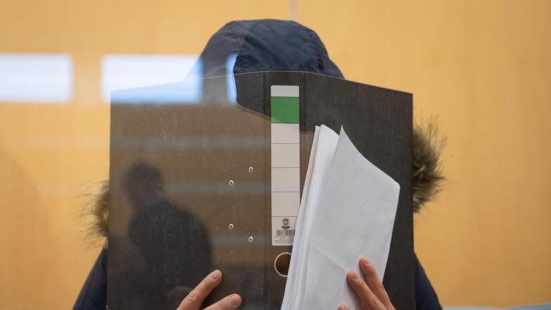 Die Angeklagte verbirgt im Düsseldorfer Oberlandesgericht ihr Gesicht hinter einem Aktenordner. Foto: Bernd Thissen/dpa