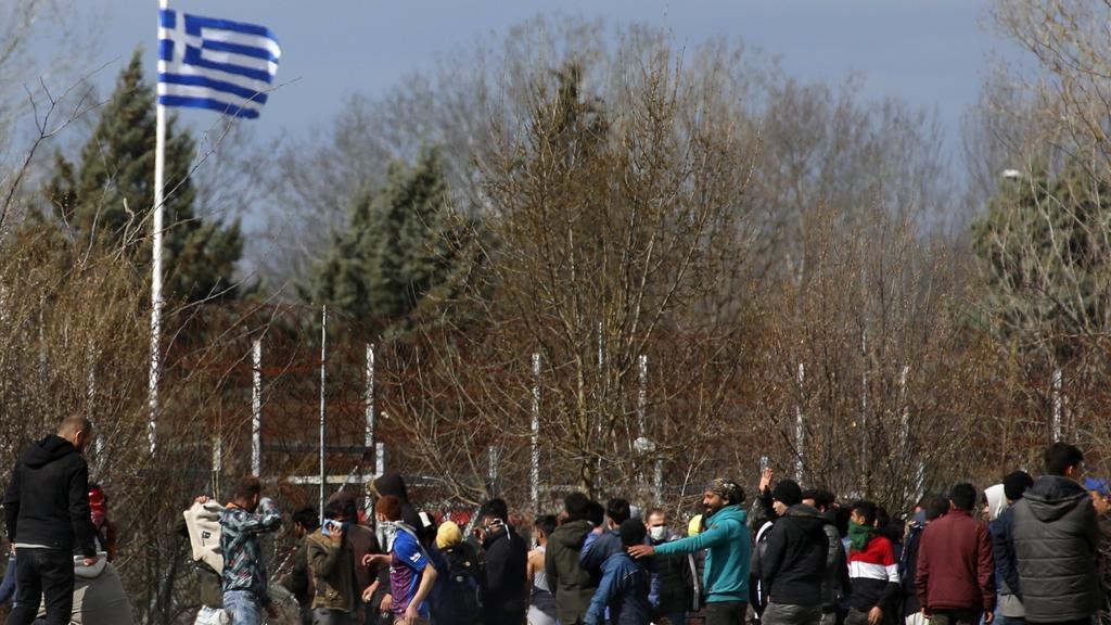 07.03.2020, Türkei, Pazarkule: Migranten stehen auf türkischer Seite vor dem Grenzzaun zu Griechenland. Tausende von Flüchtlingen und anderen Migranten haben in der vergangenen Woche versucht, in das EU-Mitglied Griechenland zu gelangen, nachdem die