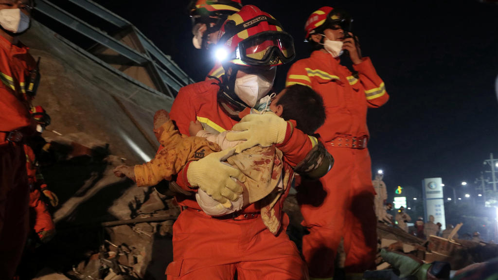 A worker wearing a face mask rescues a child at the site where a hotel being used for the coronavirus quarantine collapsed, in the southeast Chinese port city of Quanzhou, Fujian province, China March 8, 2020. China Daily via REUTERS ATTENTION EDITOR