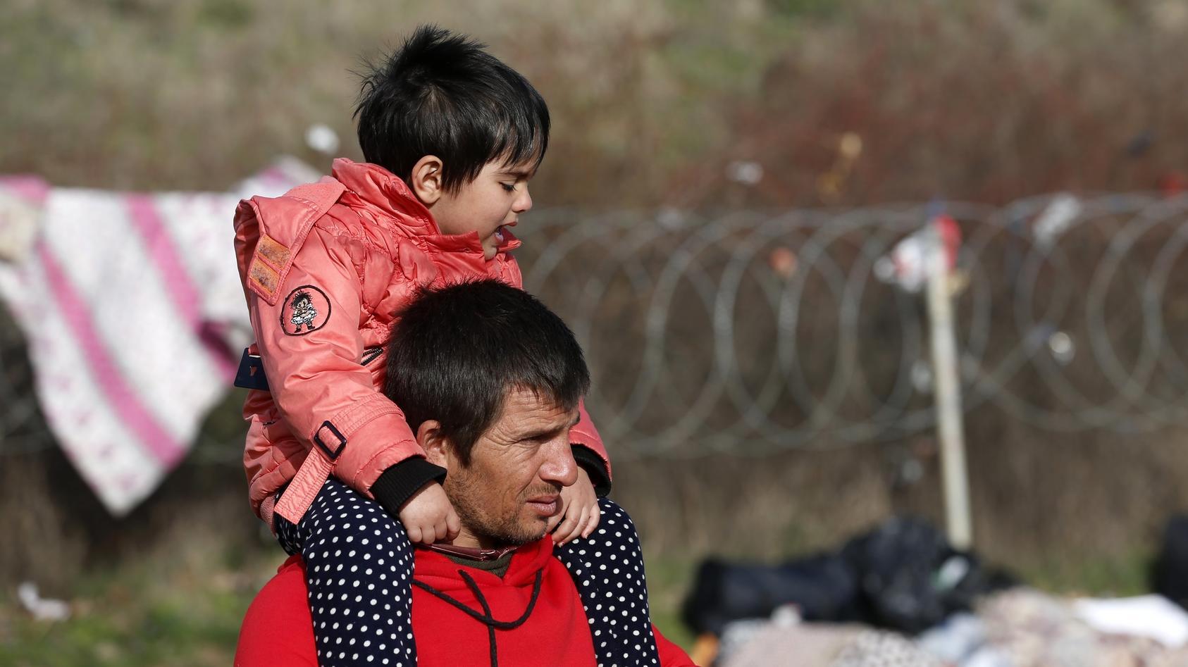 Ein Mann trägt seinen Sohn auf einem Feld nahe der türkisch-griechischen Grenze auf der Schulter.