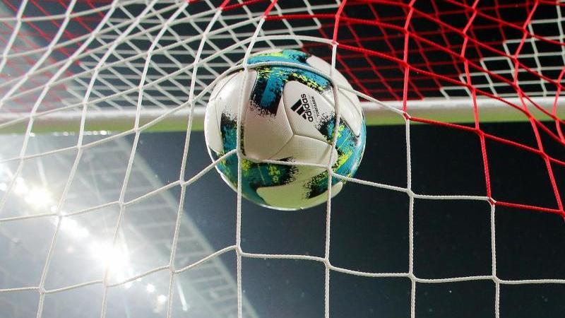 Ein Fußball fliegt ins Netz. Foto: Jan Woitas/zb/dpa/Archivbild