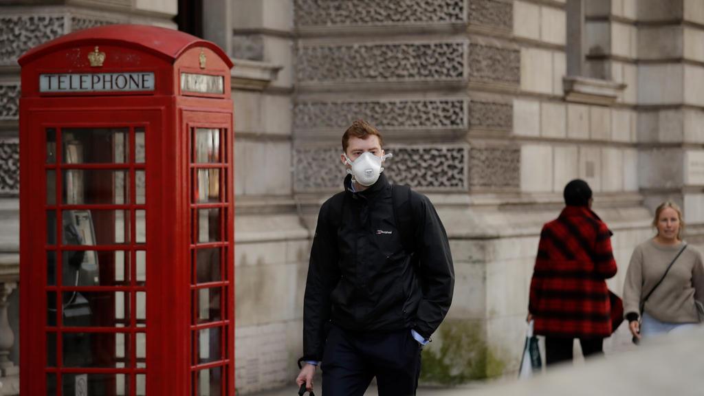 11.03.2020, Großbritannien, London: Ein Mann mit Mundschutz geht an einer roten Telefonzelle in der Nähe des Parliament Square vorbei. Foto: Matt Dunham/AP/dpa +++ dpa-Bildfunk +++
