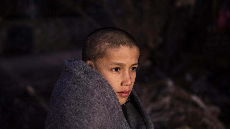 Ein Junge sitzt in Decken eingewickelt in der Nähe eines Dorfes auf Lesbos. Mehrere EU-Staaten, unter ihnen Deutschland, wollen Griechenland mindestens 1600 unbegleitete minderjährige Migranten und andere Flüchtlinge abnehmen. Foto: Angelos Tzortzinis/dpa
