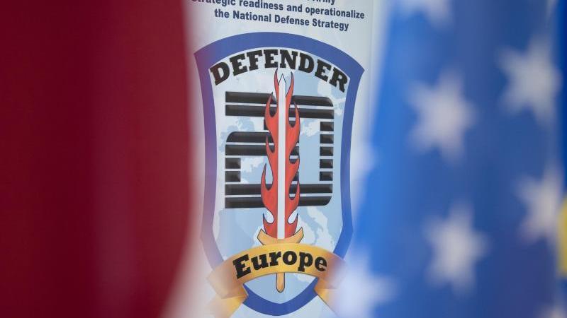 """Ein Poster mit der Aufschrift """"Defender Europe 20"""" hängt bei einer Pressekonferenz. Foto: Sebastian Kahnert/dpa-Zentralbild/dpa/Archivbild"""