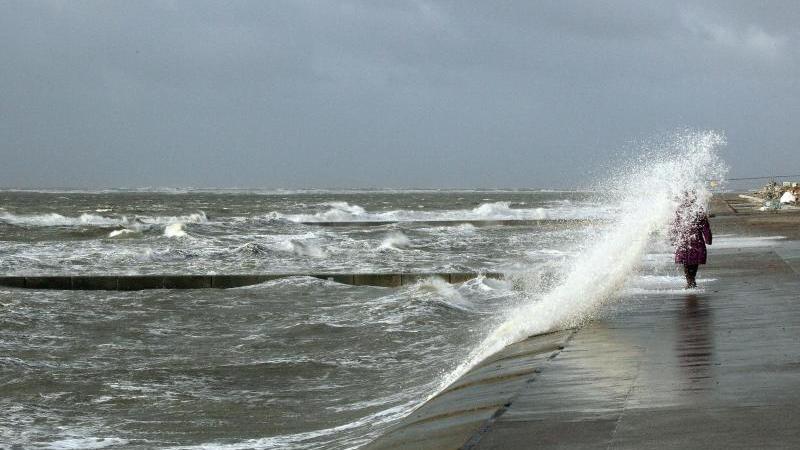Spaziergänger werden von einer Welle auf Borkum getroffen. Foto: picture alliance / dpa/Archivbild