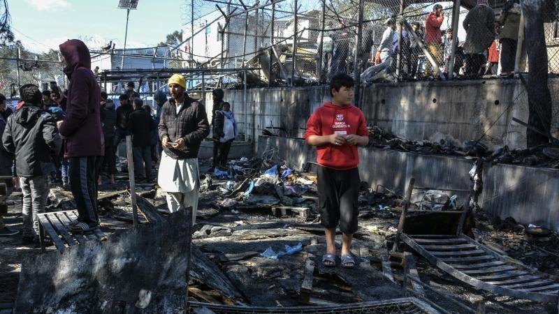 Flüchtlinge stehen im Lager Moria auf den abgebrannten Überresten eines Containerhauses. Foto: Panagiotis Balaskas/AP/dpa