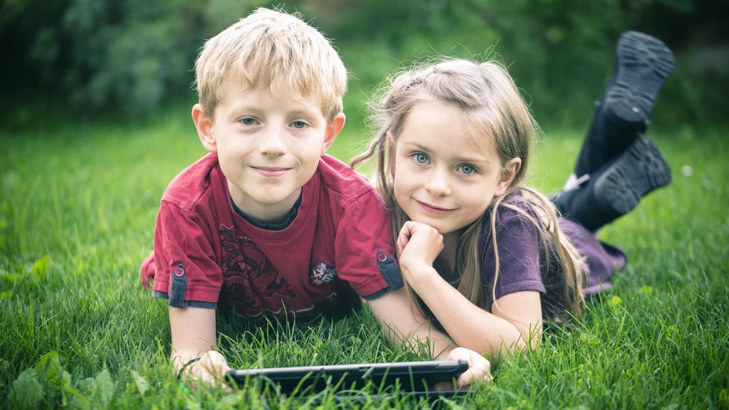 Portrait of brother and sister lying on a meadow with digital tablet model released Symbolfoto PUBLICATIONxINxGERxSUIxAUTxHUNxONLY SARF000868