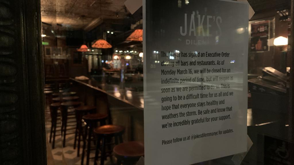 New York City: Bar geschlossen, Hinweisschild an der Tür, ungenutzte Barhocker
