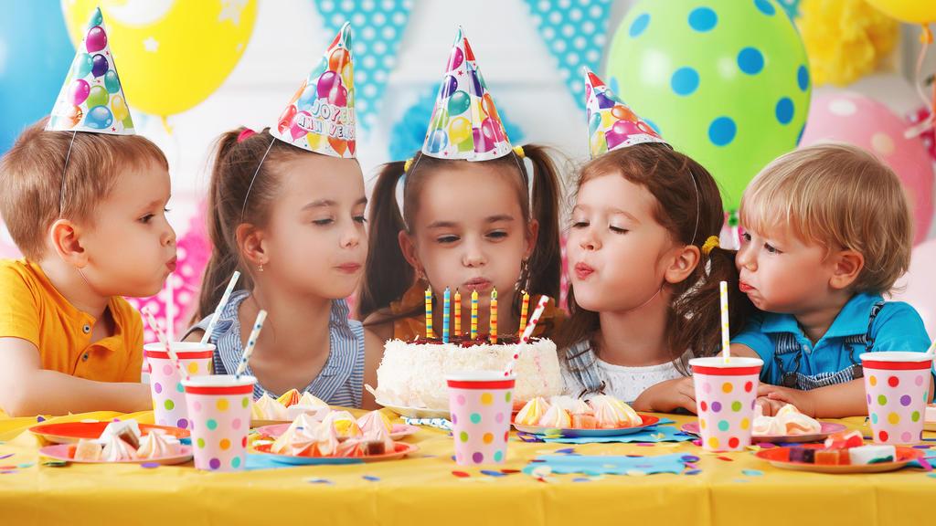 Kinder stecken die Köpfe zusammen auf Kindergeburtstag - keine gute Idee in Corona-Zeiten
