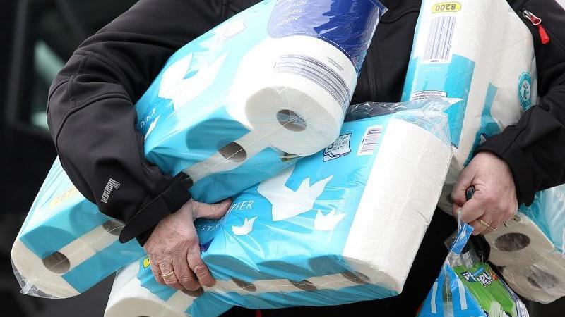 Ein Mann trägt eingekauftes Toilettenpapier und Küchenrollen aus einem Supermarkt. Foto: Rene Traut/dpa