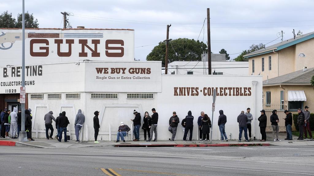 15.03.2020, USA, Culver City: Menschen warten in einer langen Schlange vor einem Waffenladen in Zeiten der raschen Ausbreitung des neuartigen Coronavirus im Land. Einige Wartende wollen sich mit Munition eindecken, während andere sagten, sie würden W