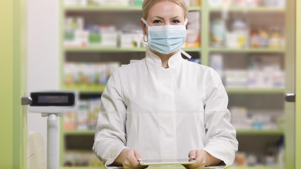 Apothekerin schützt sich mit Gesichtsmaske - Podcast zum Coronavirus