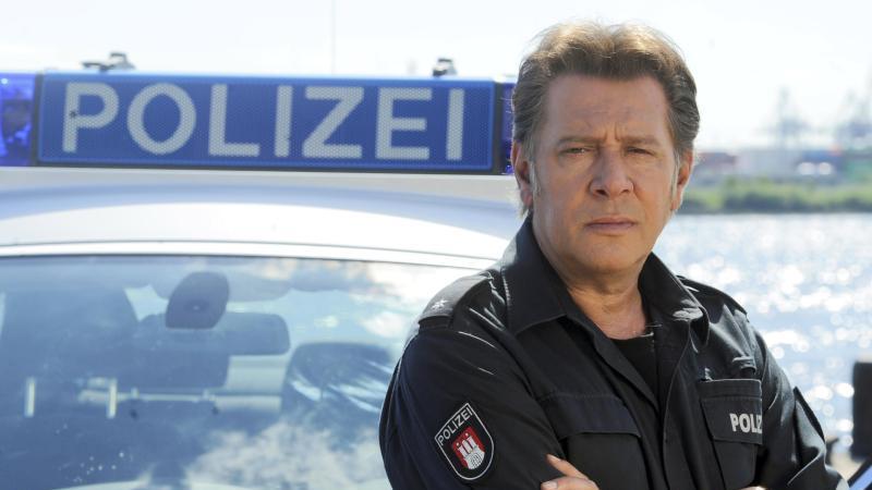 """Der Schauspieler Jan Fedder steht bei einem Fototermin zum """"Großstadtrevier"""" an einem Polizeiwagen. Foto: Fabian Bimmer/dpa"""
