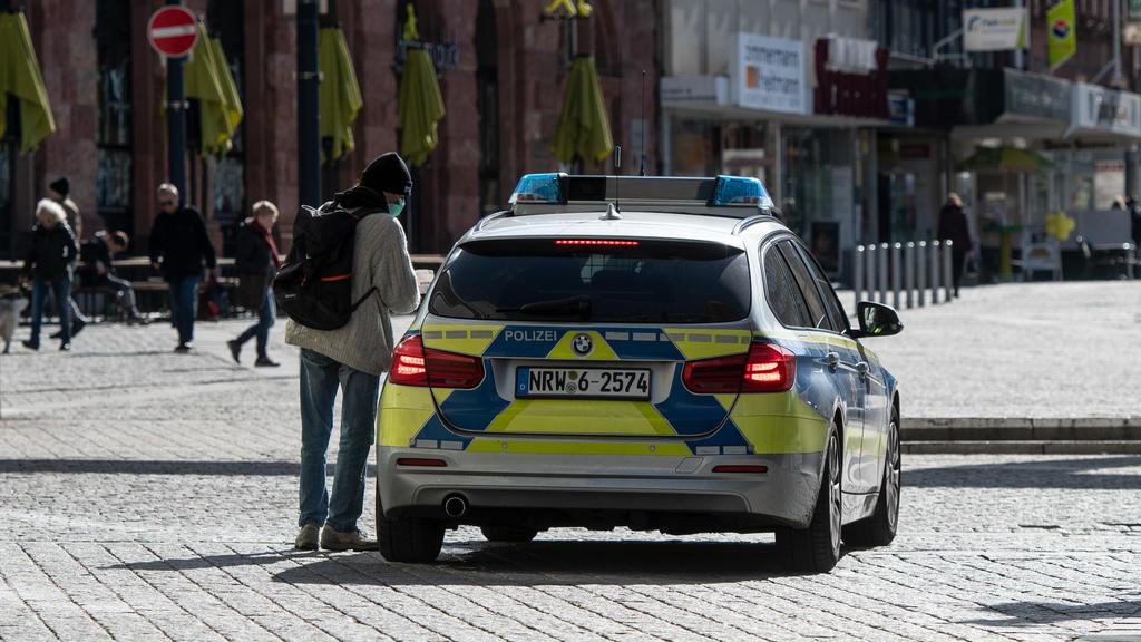 ARCHIV - 23.03.2020, Nordrhein-Westfalen, Dortmund: Ein Mann mit einem Mundschutz unterhält sich in der Fußgängerzone mit den Polizisten in einem Streifenwagen. Nordrhein-Westfalen hat einen Bußgeldkatalog für Verstöße gegen die landesweiten Corona-R