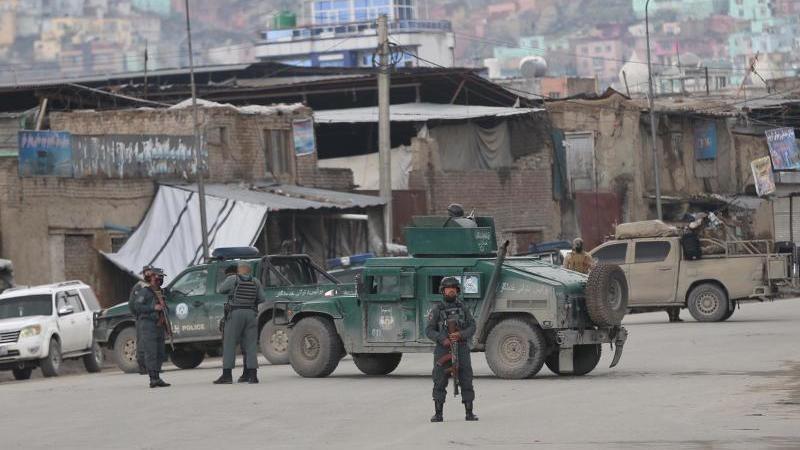 """Die afghanische Polizei am Ort des Geschehens: """"""""Bislang haben wir keine Nachrichten aus dem Inneren."""". Foto: Rahmat Gul/AP/dpa"""