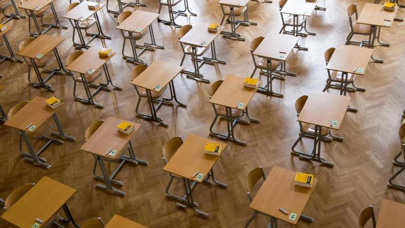 Durchnummerierte Tische stehen in einer Aula. Foto: Peter Kneffel/dpa/Archivbild