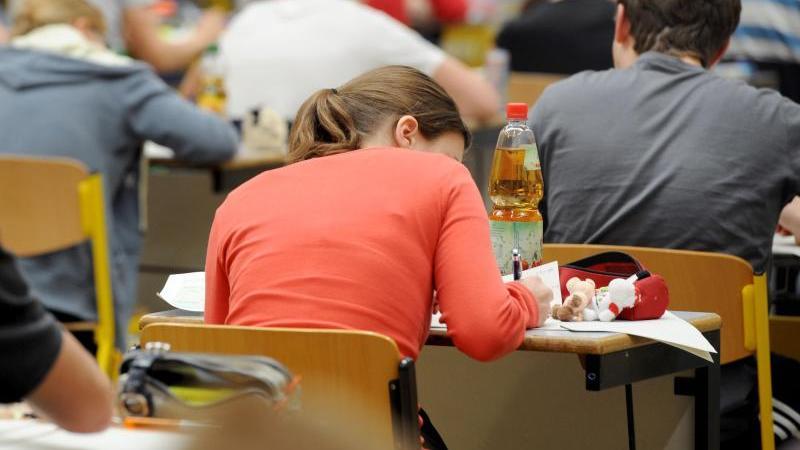 Abiturienten schreiben in einer Turnhalle die Abiturprüfung in Deutsch. Foto: Armin Weigel/dpa/Archivbild