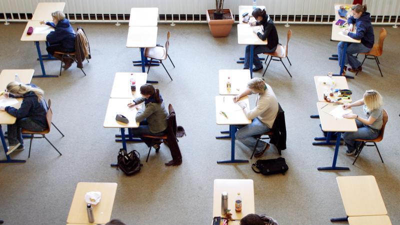 Schüler und Schülerinnen absolvieren eine Prüfung. Foto: Roland Weihrauch/dpa/Symbolbild