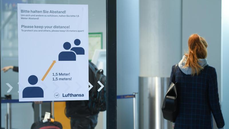 """Bitte halten Sie Abstand !"""" steht auf einem Plakat im Terminal 1 des Frankfurter Flughafens. Foto: Arne Dedert/dpa"""