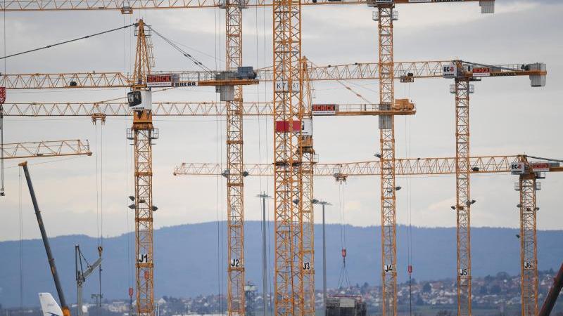 Zahlreiche Baukräne ragen auf einer Baustelle in die Höhe. Foto: Arne Dedert/dpa/Archivbild/Symbolbild