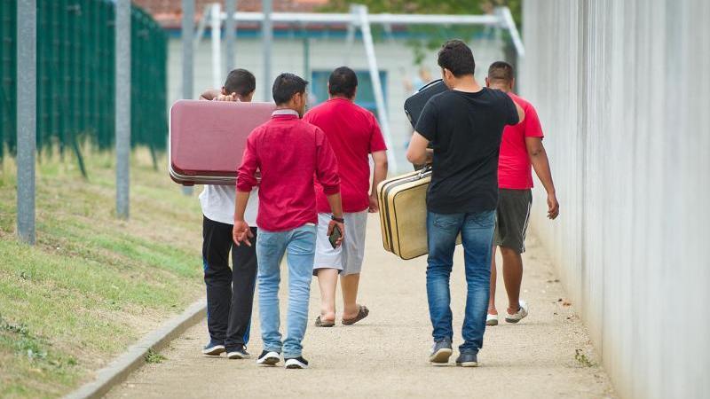 Männer gehen auf einem Weg zu einer Aufnahmeeinrichtung für Flüchtlinge. Foto: Christoph Schmidt/dpa/Archivbild