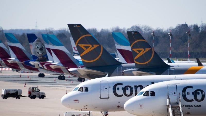 Zahlreiche Flugzeuge von Condor und Eurowings stehen auf dem Vorfeld eines Flughafens geparkt. Foto: Federico Gambarini/dpa