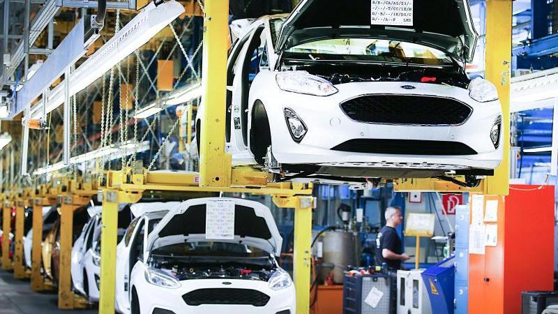 Fahrzeuge vom Typ Ford Fiesta fahren am Fließband durch die Werkhalle. Foto: Oliver Berg/dpa/Archivbild