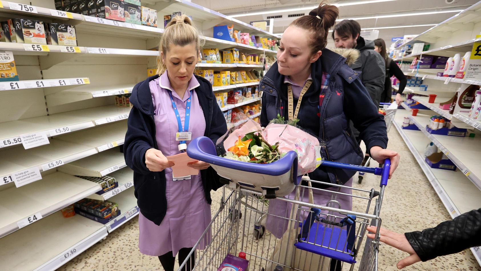 """Zwei freiwillige Helferinnen des britischen Gesundheitsdienstes """"NHS"""" im Supermarkt."""