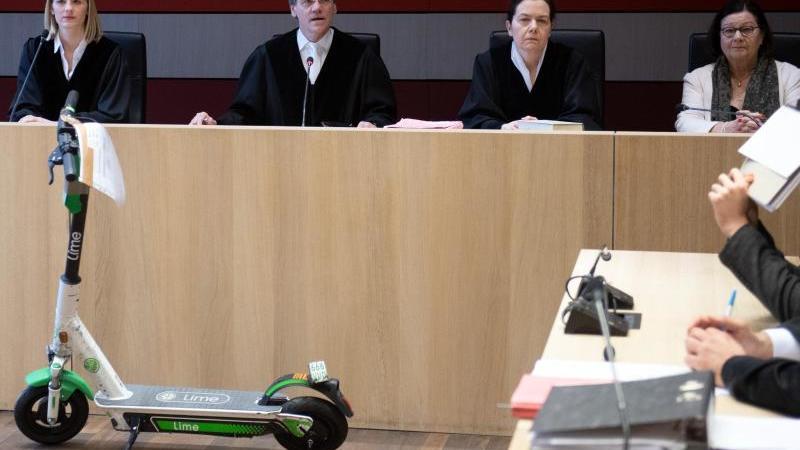 Ein E-Scooter steht als Beweismittel vor Johannes Kirfel (2.v.l), Richter im Landgericht. Foto: Bernd Thissen/dpa/Archivbild