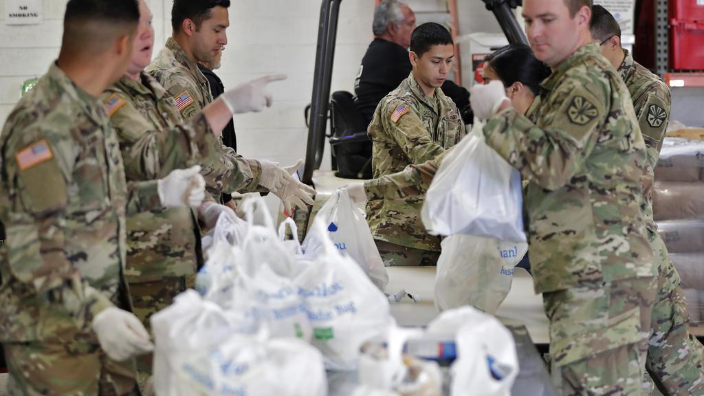 26.03.2020, USA, Mesa: Mitglieder der Nationalgarde von Arizona packen und sortieren Lebensmittel in einer Lebensmittelbank Foto: Matt York/AP/dpa +++ dpa-Bildfunk +++