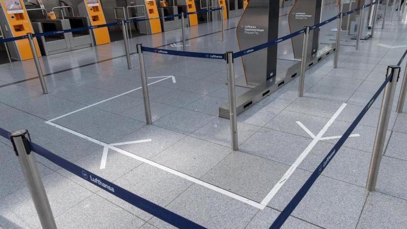 Check-In-Personal der Lufthansa wartet an der Gepäckkontrolle am Flughafen München auf die Passagiere. Foto: Peter Kneffel/dpa/Archivbild