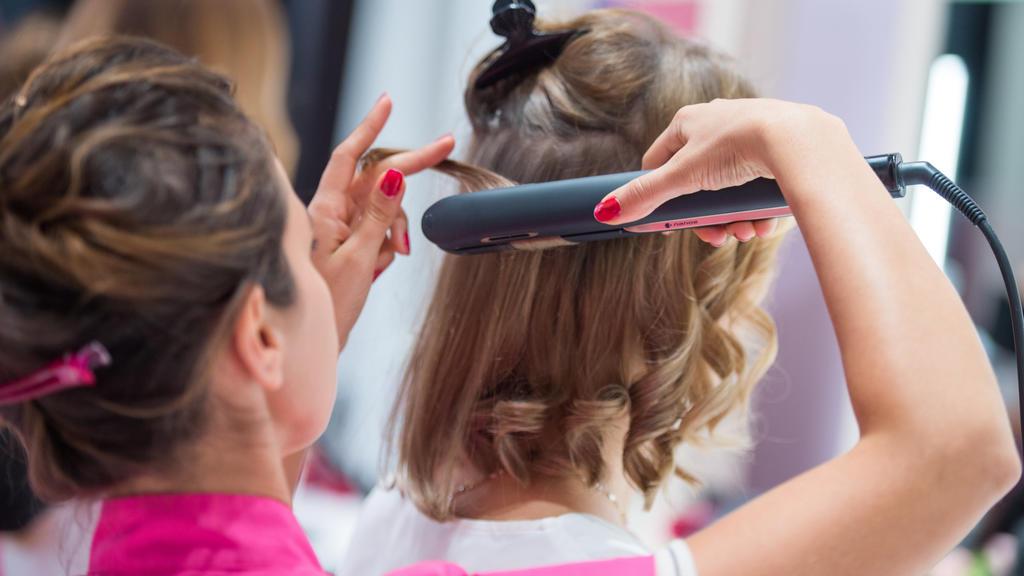 ARCHIV - 05.09.2018, Berlin: Einer Frau werden in einem Friseursalon die Haare geglättet. In einer Gesprächsrunde soll der frage nachgegangen werden, wie sich die Situation von Frauen auf dem Arbeitsmarkt in den vergangenen Jahren verändert hat (zu d