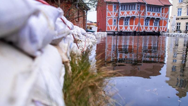 Ein Fachwerkhaus steht über dem überfluteten Mühlenbach, an dessen Ufer Sandsäcken ausgelegt sind. Foto: Jens Büttner/dpa-Zentralbild/dpa