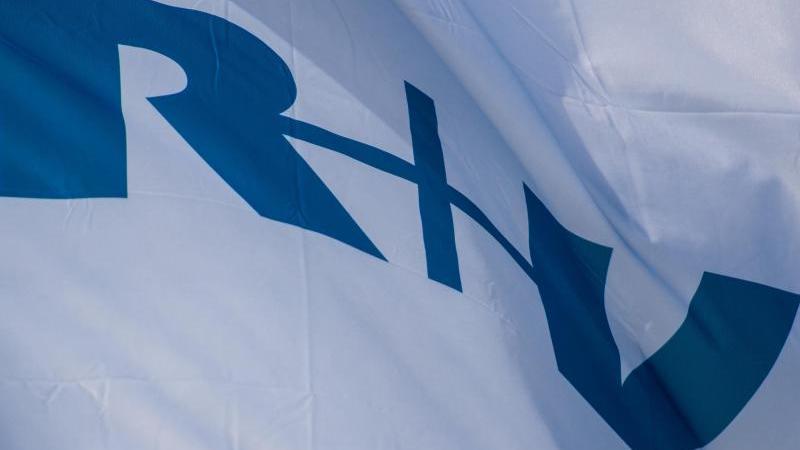 """Eine Fahne mit dem Logo """"R+V"""" vor der Firmenzentrale des Versicherungs-Unternehmens. Foto: Andreas Arnold/dpa/Archivbild"""