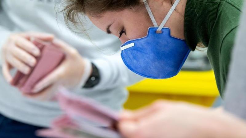 Eine Wahlhelferin trägt Schutzmaske, während sie die Auszählung der Briefwahl vorbereitet. Foto: Sven Hoppe/dpa
