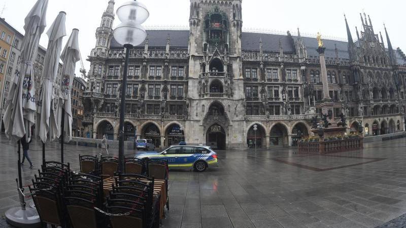 Vor dem Müncher Rathaus fährt ein Polizeiauto über den leeren Marienplatz. Foto: Felix Hörhager/dpa