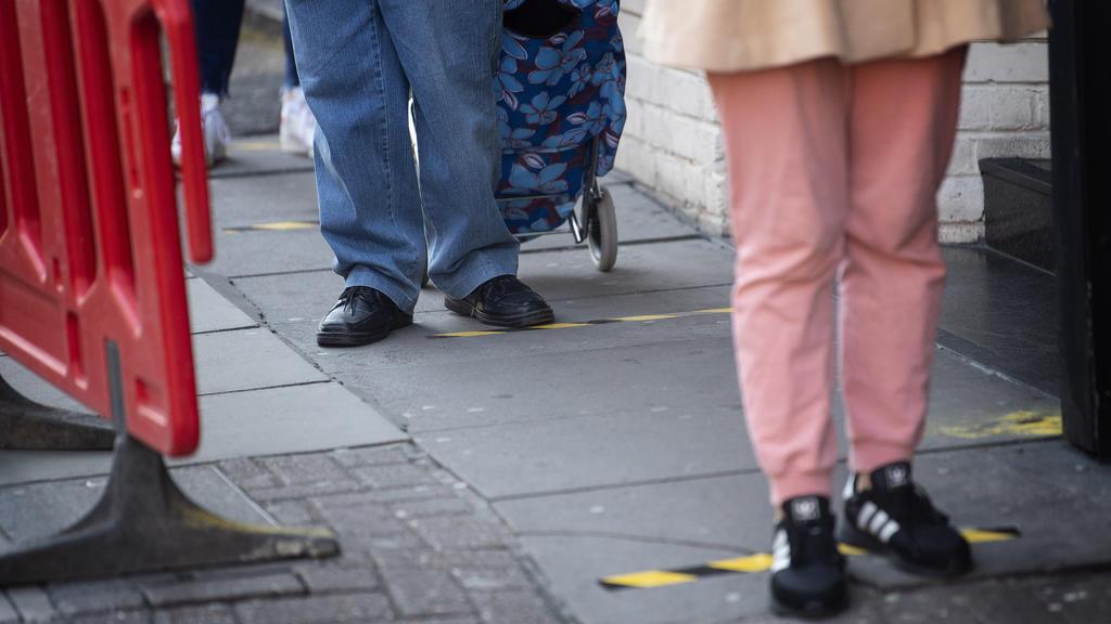 26.03.2020, Großbritannien, London: Kunden stehen vor einem Supermarkt in Westminster Schlange, vor dem Klebeband auf dem Boden angebracht ist, um die Einhaltung eines Mindestabstandes zwischen den Kunden zu gewährleisten. Der britische Premier Johns
