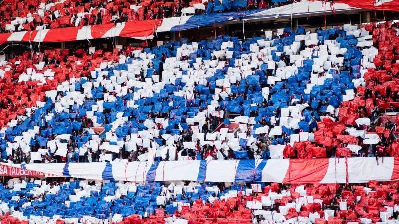 Fans halten blaue, weiße und rote Zettel hoch, die zusammen das Logo des FC Bayern ergeben. Foto: Matthias Balk/dpa/Archivbild