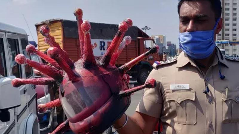 Der Polizist trägt einen Mundschutz und hält in der Hand einen roten Helm, der wie das Corona-Virus aussieht.