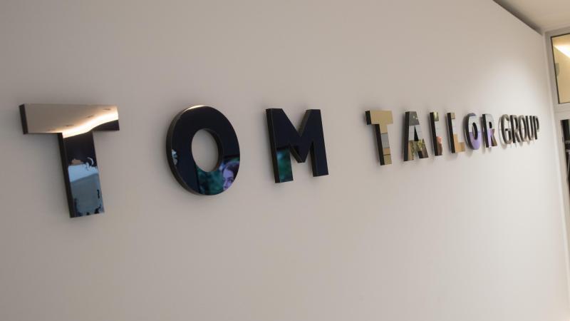 Der Schriftzug der Modekette Tom Tailor Group im Eingangsbereich der Zentrale der Modekette. Foto: Christian Charisius/dpa/Archivbild
