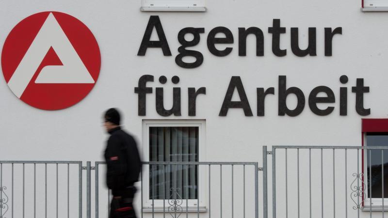 Ein Mann geht an dem Logo der Agentur für Arbeit vorbei. Foto: Sebastian Kahnert/dpa-Zentralbild/dpa/Archivbild