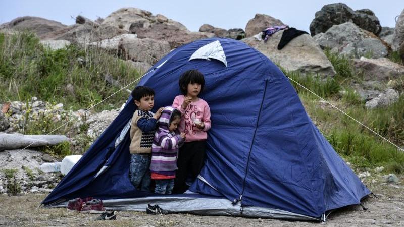 Flüchtlings-Kinder stehen vor einem Zelt im Dorf Petra auf der nordöstlichen Ägäisinsel Lesbos. Foto: Panagiotis Balaskas/AP/dpa
