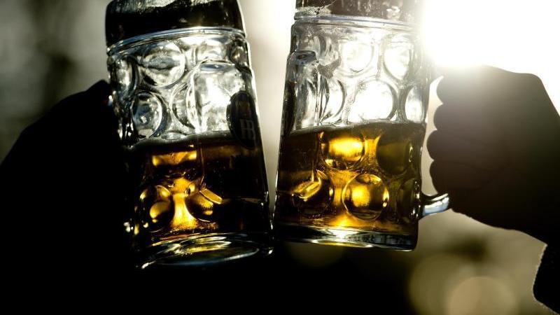 Zwei Frauen stoßen mit Bierkrügen an. Foto: picture alliance / dpa / Illustration